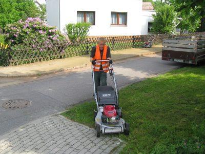 Ein beschäftigter Mensch Mäht den Rasen mit einem Rasenmäher