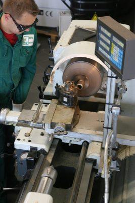 Nahaufnahme von einem Menschen der eine mechanische Maschine bedient